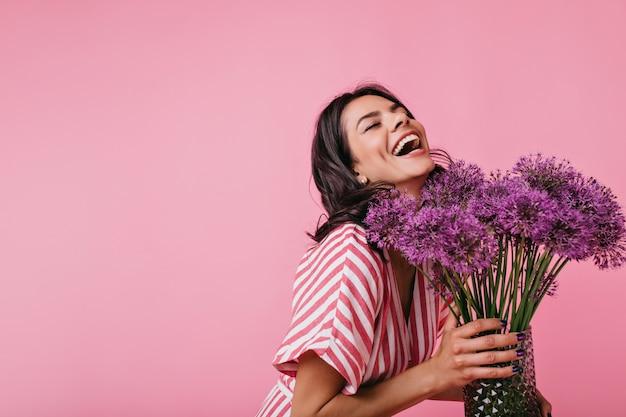 Menina com vestido de verão rosa gosta de perfume de flores e ri sinceramente, aproveitando o ótimo dia de primavera.