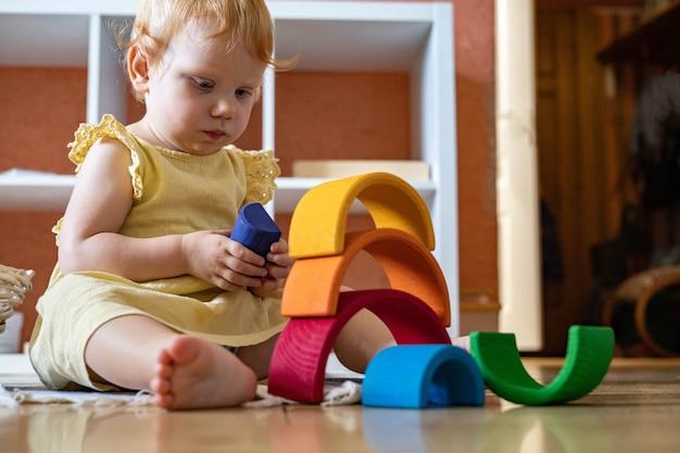 Menina com vestido empilhando arco-íris bloco construção edifício torre de brinquedo de madeira ecológica