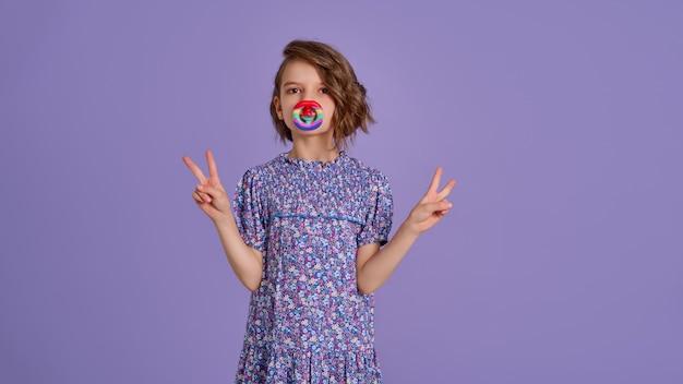 Menina com vestido estampado de flor azul de verão segurando um brinquedo antiestresse na alfazema