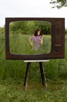 Menina com vestido floral andando no jardim dentro da moldura da televisão vintage