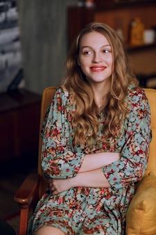 Menina com vestido floral outono inverno sentado e sorrindo.