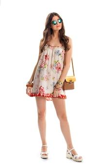 Menina com vestido floral sem mangas. sandálias de cunha e bolsa bicolor. óculos de sol estilo camaleão. nova tendência de verão.
