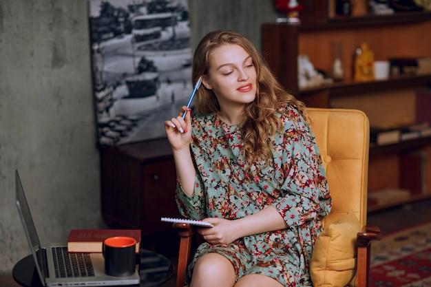 Menina com vestido floral sentado e fazendo anotações em seu caderno.