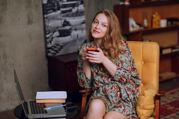 Menina com vestido floral sentado e segurando uma caneca de café marrom.