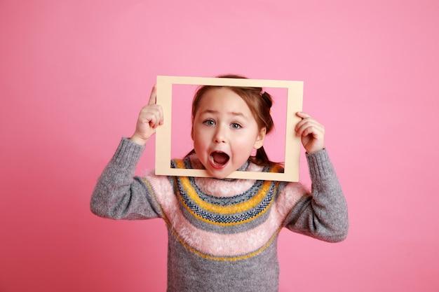 Menina com vestido quente olhando através do quadro na rosa bachground.