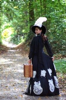 Menina com vestido retrô do século 18 com valise no parque