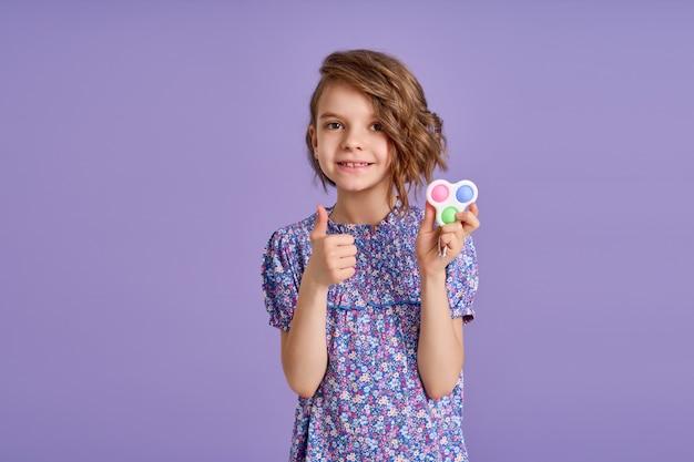 Menina com vestido roxo e um brinquedo popit com ela batendo no fundo roxo