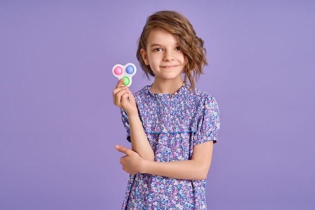 Menina com vestido roxo e um brinquedo popit em fundo roxo