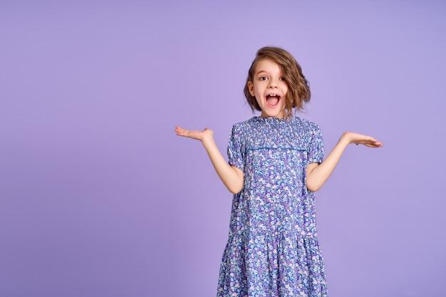 Menina com vestido roxo parecendo surpresa no fundo roxo