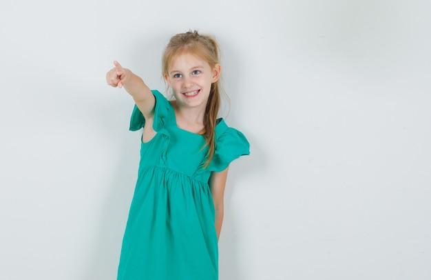 Menina com vestido verde apontando o dedo para longe e parecendo alegre