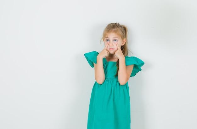 Menina com vestido verde puxando para baixo as pálpebras e parecendo calada