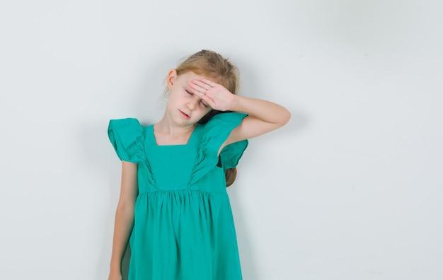 Menina com vestido verde segurando a mão na testa e parecendo com sono