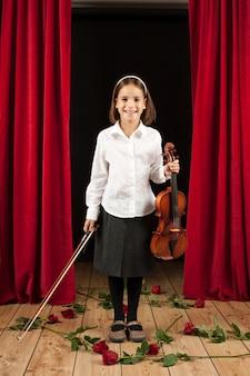 Menina com violino no teatro de palco