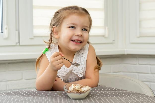 Menina come ansiosamente sorvete de bolinhos em uma mesa da cozinha e fica feliz