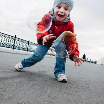 Menina come bolhas de sabão no cais