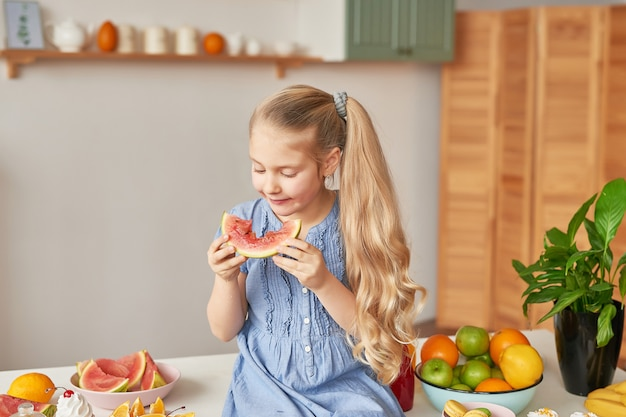 Menina come frutas na cozinha