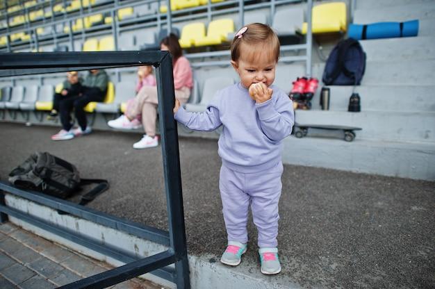 Menina come maçã. jovem mãe elegante com quatro filhos sentados no pódio de esportes no estádio. a família passa o tempo livre ao ar livre com patinetes e patins.