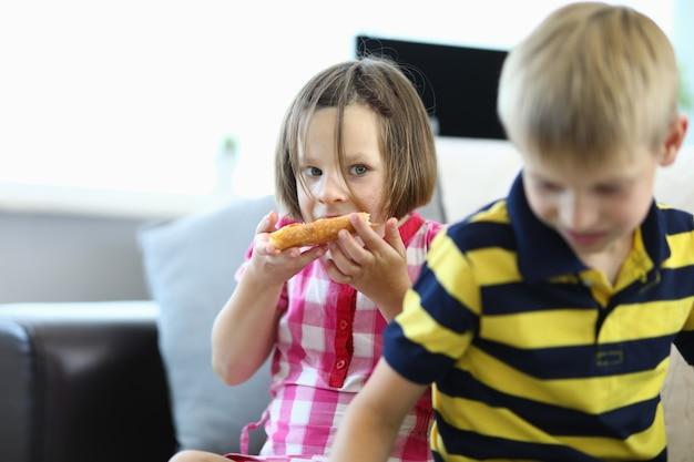Menina come pizza, um menino está parado ao lado dela.