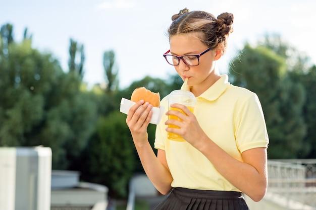 Menina come sanduíche e bebe suco de laranja