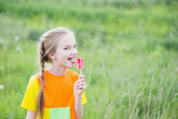 Menina come sorvete no verão