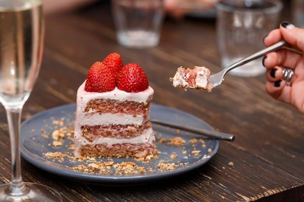 Menina come um bolo doce com frutas de verão em uma mesa de madeira. festa, mesa doce. verão oferecer sobremesas no restaurante.