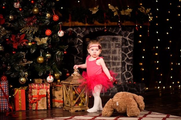 Menina comemora ano novo perto da árvore de natal em casa.