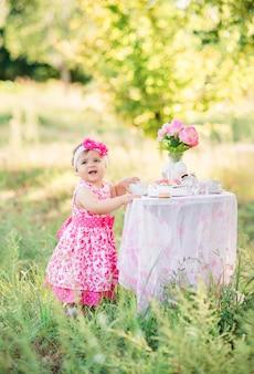 Menina comemora seu primeiro aniversário com bolo e balões na natureza