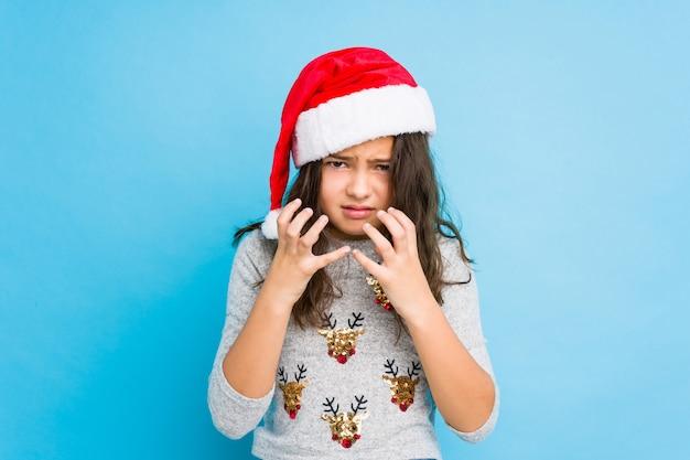 Menina comemorando o dia de natal chateado gritando com mãos tensas.