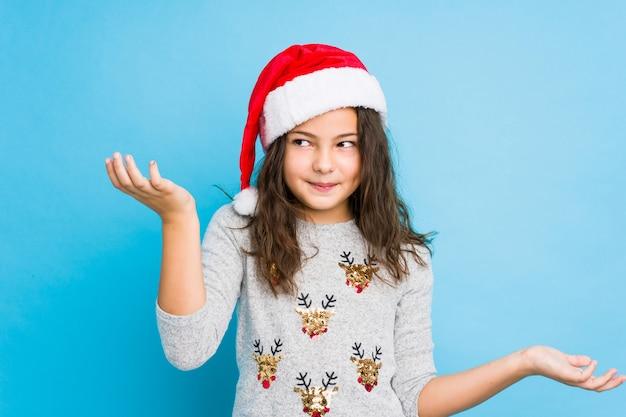Menina comemorando o dia de natal, duvidando e encolher os ombros os ombros em questionar o gesto.