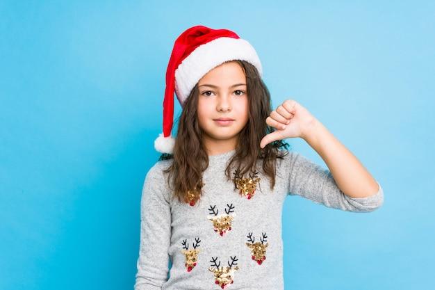 Menina comemorando o dia de natal, mostrando um gesto de antipatia, polegares para baixo. conceito de desacordo.