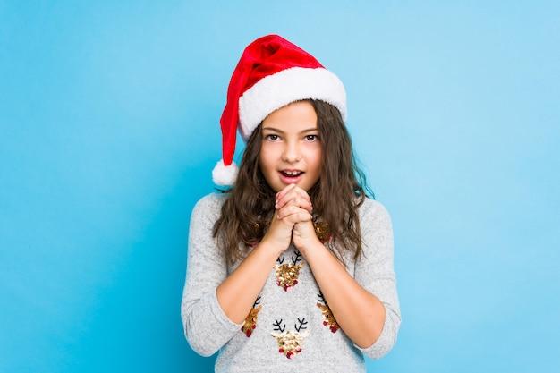 Menina comemorando o dia de natal rezando para dar sorte, boca espantada e abertura, olhando para a frente.