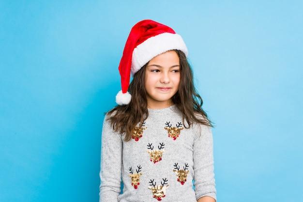Menina comemorando o dia de natal ri e fecha os olhos, sente-se relaxado e feliz.