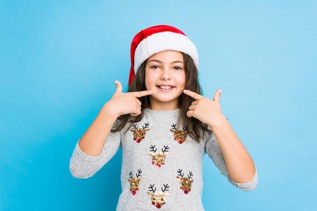 Menina comemorando o dia de natal sorri, apontando os dedos na boca.