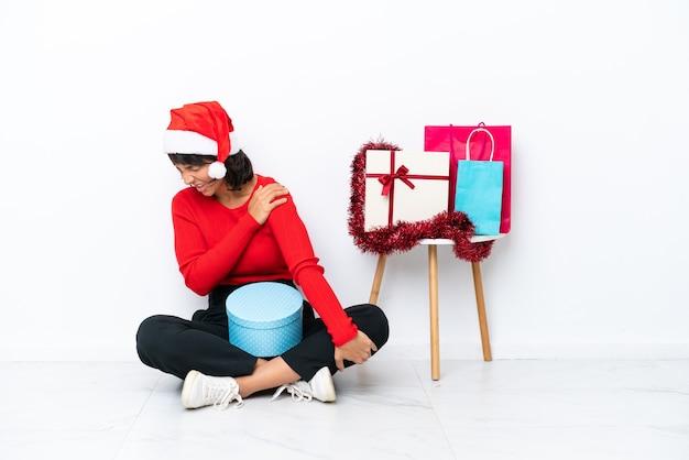 Menina comemorando o natal sentada no chão, isolada no fundo branco, sofrendo de dor no ombro por ter feito um esforço
