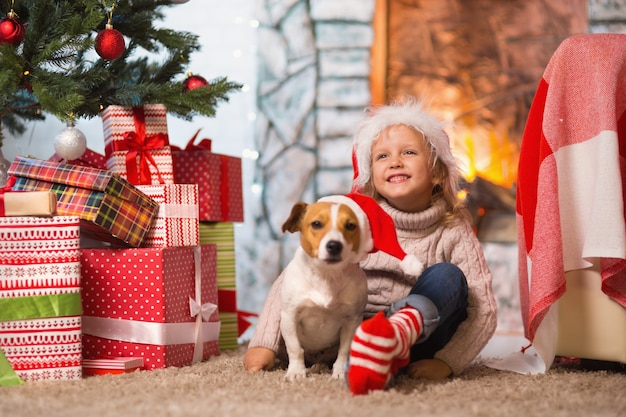Menina comemorando um feliz natal em casa junto à lareira com um cachorro de estimação jack russell