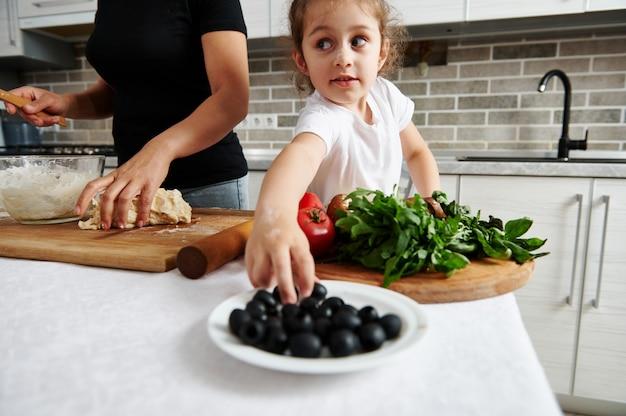 Menina comendo azeitonas, ingrediente de pizza, enquanto a mãe prepara massa de pizza