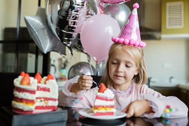 Menina comendo bolo de aniversário