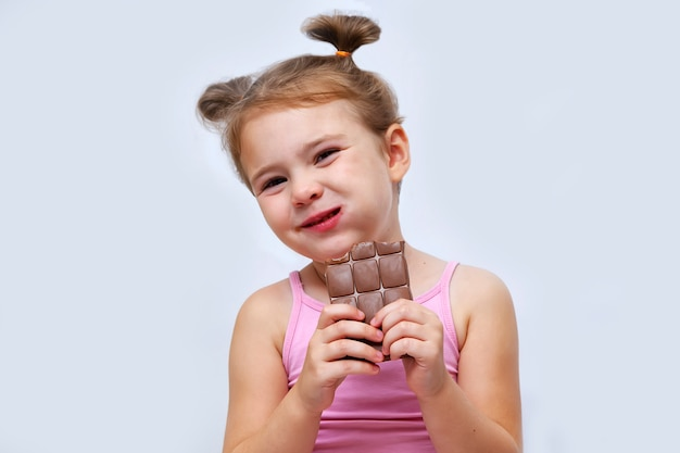Menina comendo chocolate isolado no branco