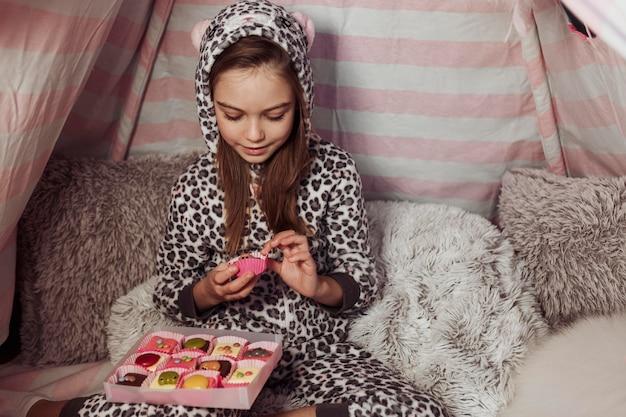 Menina comendo doces em uma barraca dentro de casa