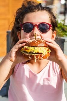 Menina comendo hambúrguer na rua.