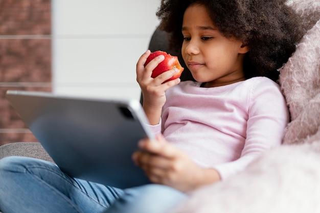 Menina comendo maçã e usando tablet