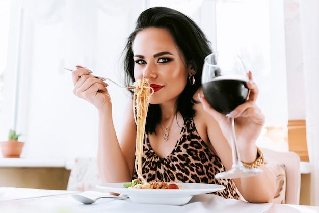 Menina comendo macarrão em um restaurante, bebendo seu vinho tinto
