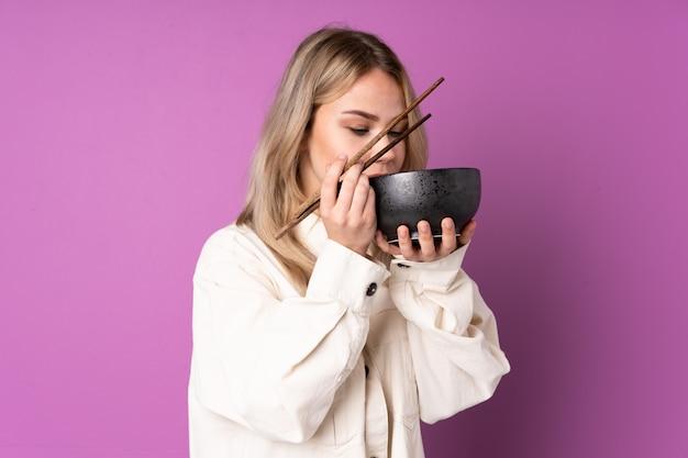 Menina comendo macarrão na parede roxa