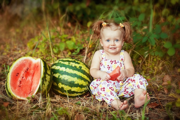 Menina comendo melancia. o conceito de desenvolvimento infantil e alimentação saudável.