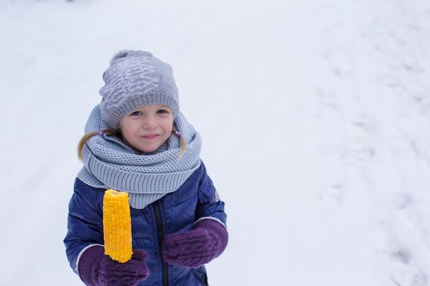 Menina comendo milho ao ar livre no dia de inverno
