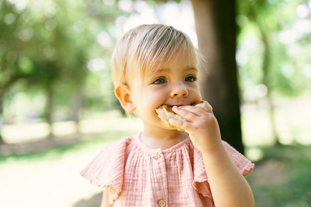 Menina comendo panqueca em um gramado verde