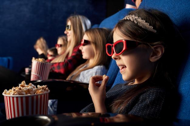 Menina comendo pipoca, assistindo desenhos animados no cinema.