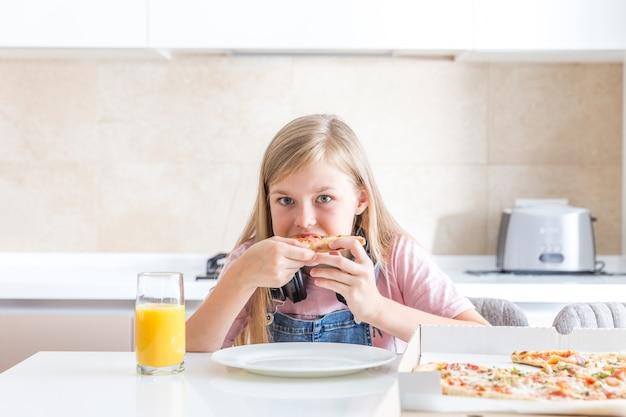 Menina comendo pizza sentado à mesa