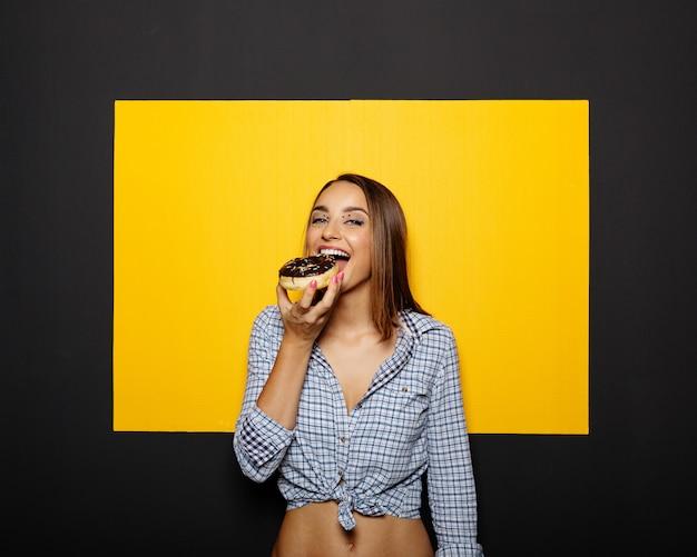 Menina comendo rosquinha com cobertura de chocolate