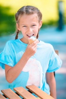 Menina comendo sorvete ao ar livre no verão no café ao ar livre